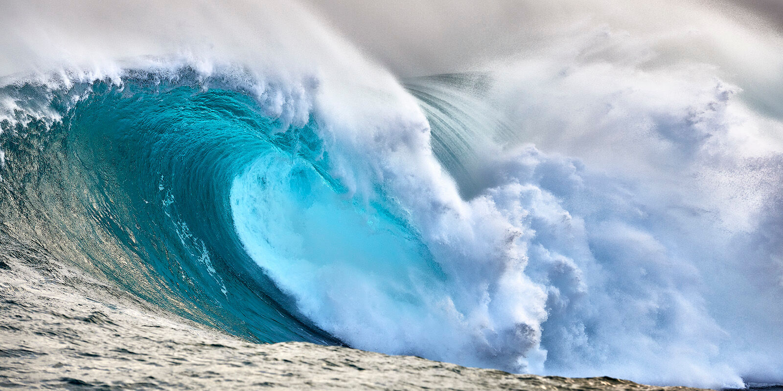 an emerald colored panoramic photograph of the biggest wave in Hawaii Jaws on the island of Maui.  Photographed by Andrew Shoemaker