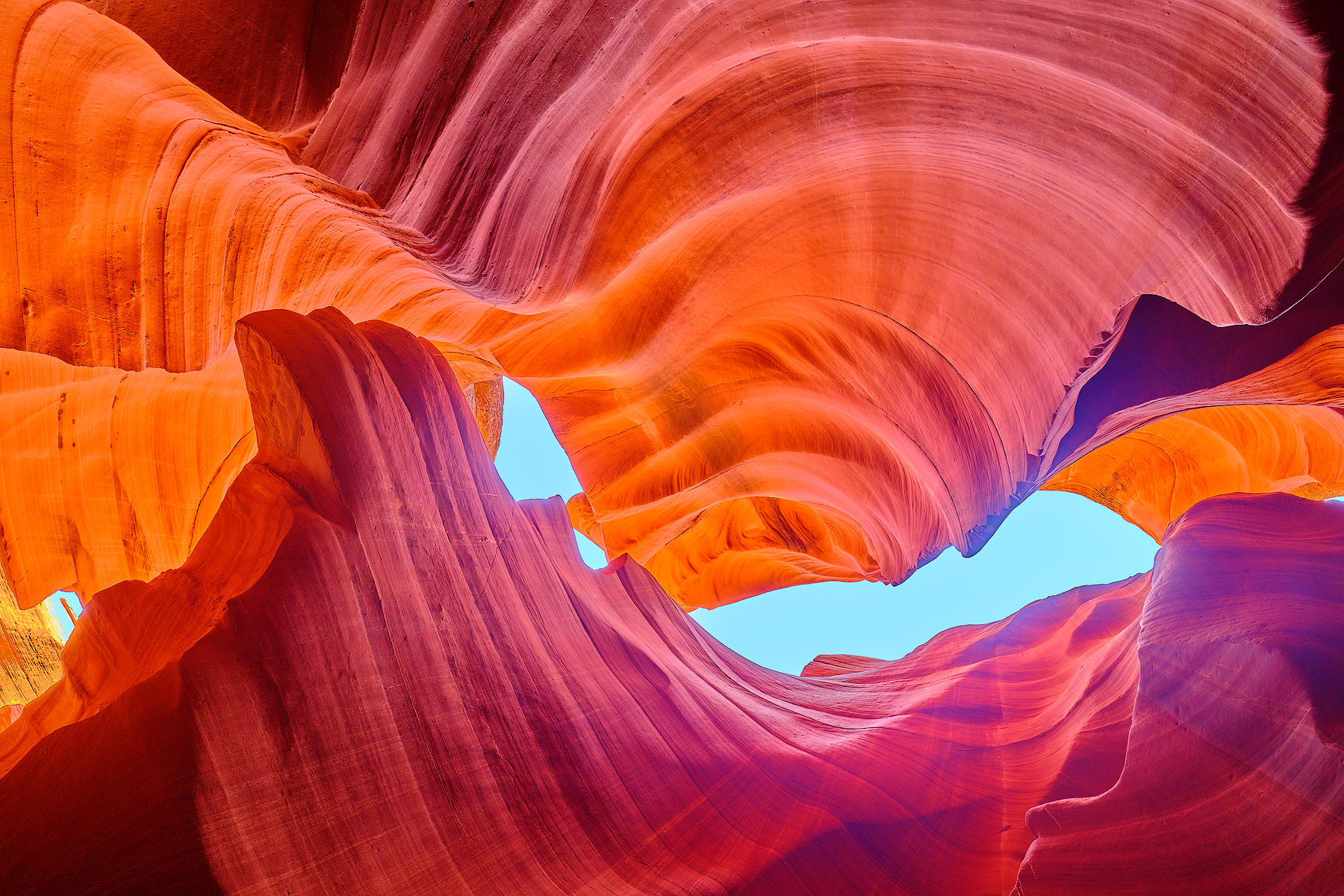 a fine art photograph from within lower antelope canyon in Arizona with orange, red, and purple colors. Fine art photography by Andrew Shoemaker