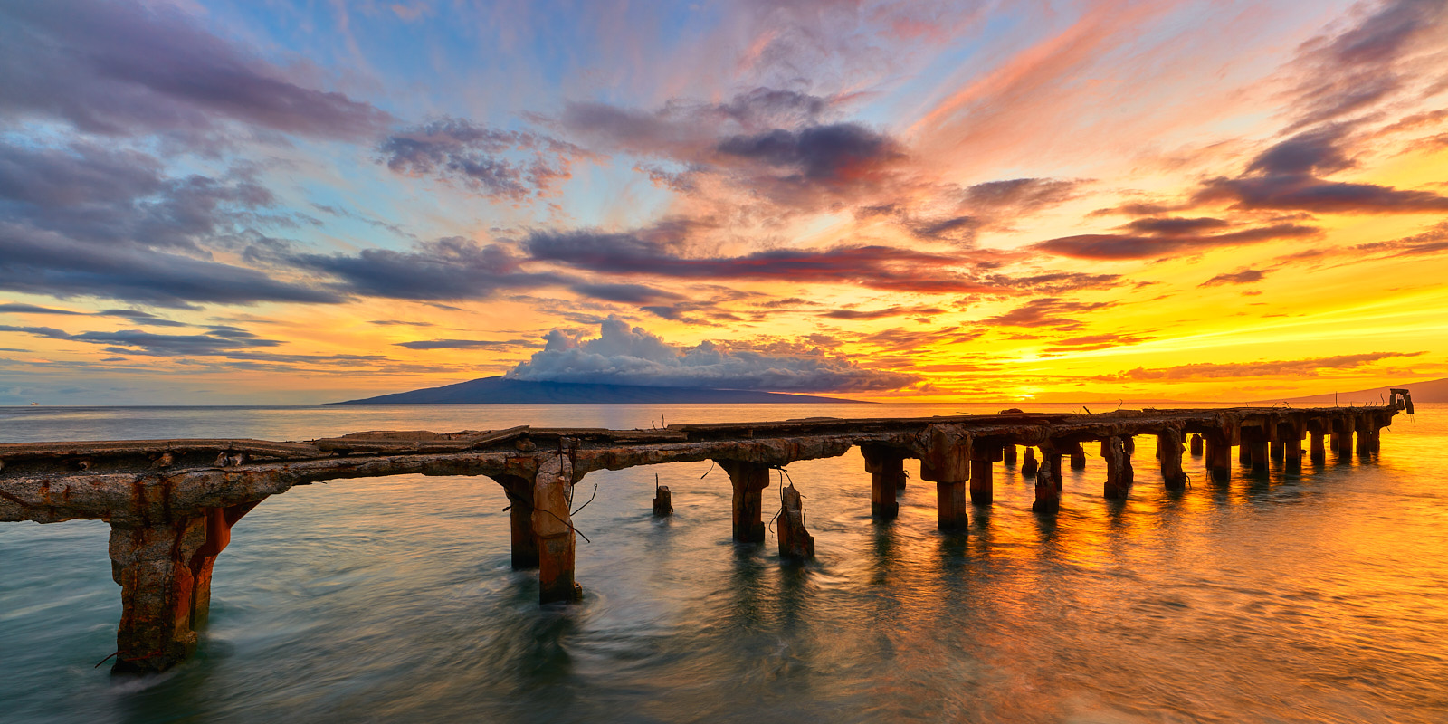 a very vibrant sunset captured at Mala Lamp extending into the ocean in Lahaina on the island of Maui.  Hawaii Panorama photographed by Andrew Shoemaker