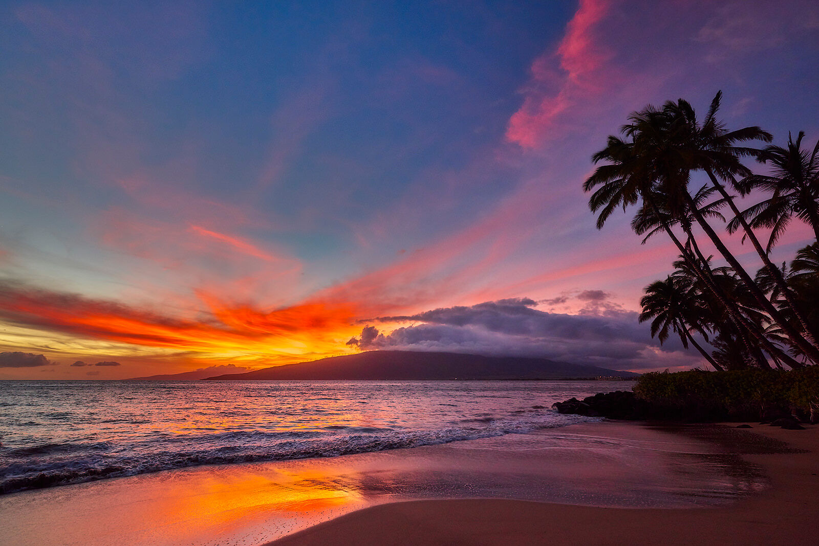 a vibrant sunset with pink, purple, and orange colors and west Maui in the background as seen from North Kihei.  Photographed by Andrew Shoemaker