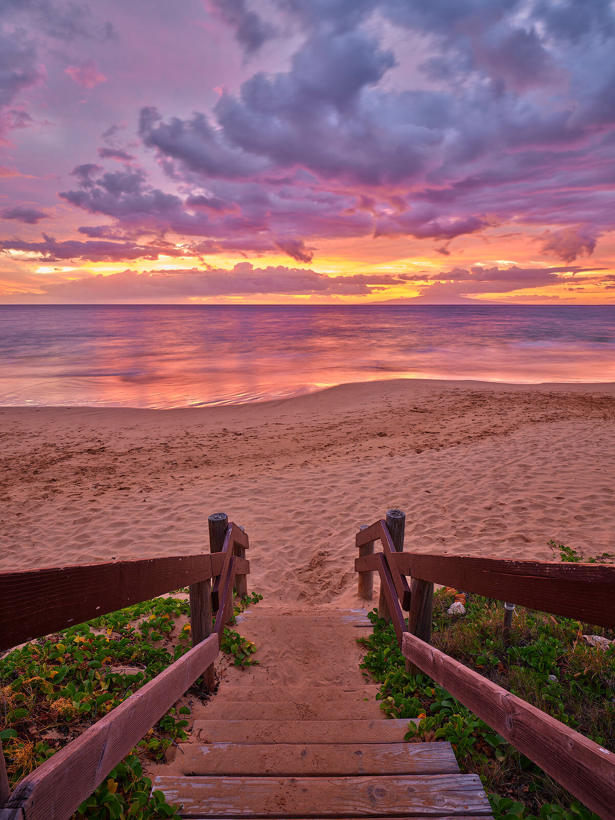 stairway down to a beautiful beach on the Hawaiian island of Maui at sunset featuring pink, purple, and orange colors.  Photographed by Andrew Shoemaker
