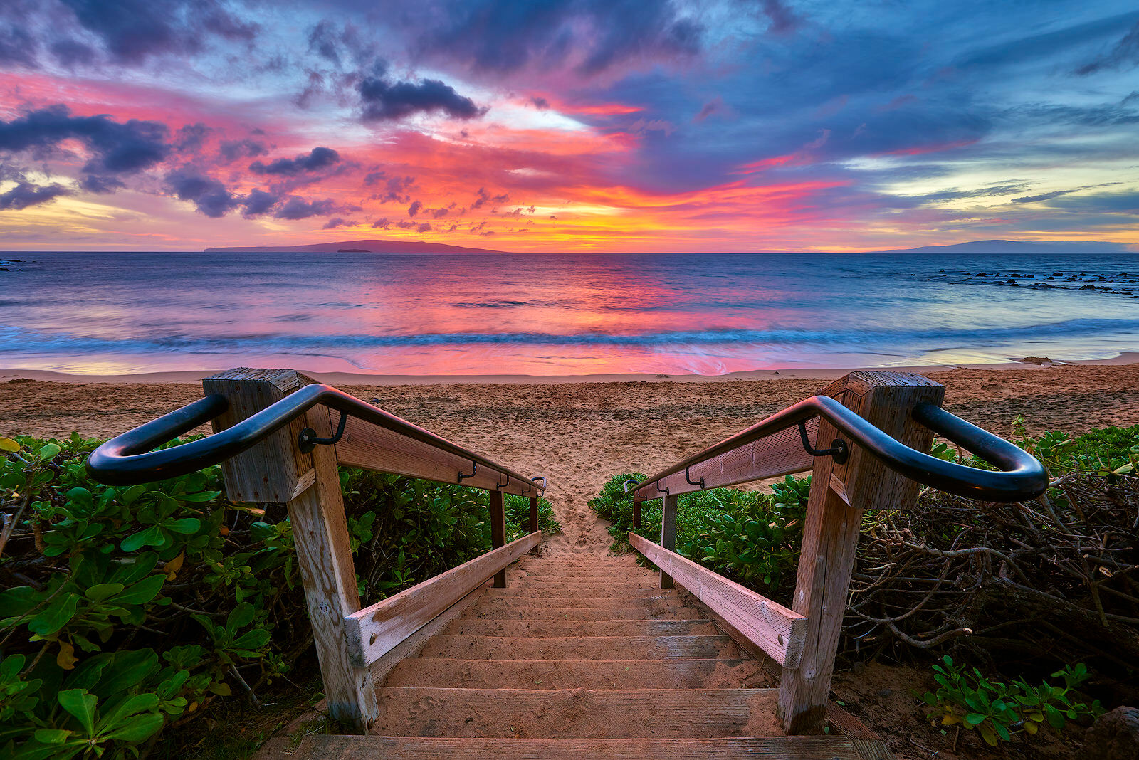 Looking down a beach staircase on to Ulua Beach in Wailea at sunset on the island of Maui.  Photographed by Andrew Shoemaker