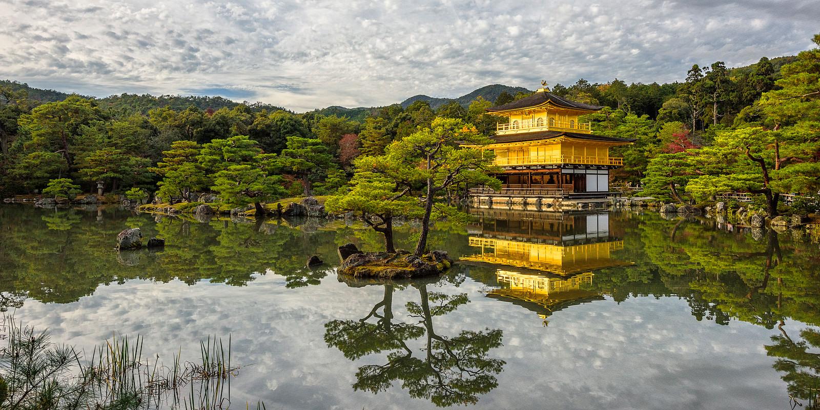 Golden Kinkaku-ji temple reflects on the water in Kyoto, Japan